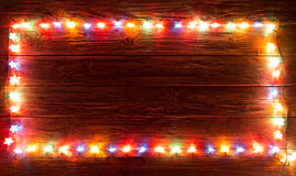 Glowing Christmas Lights Frame for Xmas Holiday Greeting Cards Design. Wooden Hand Drawn Background. Merry Christmas Stock Image