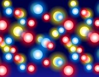 Glowing Christmas Lights Night. A background pattern of glowing Christmas lights at night in various colors set against dark blue background Stock Images