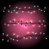 Glowing Christmas lights pink background. Christmas bulb lights on dark red pink background. Multicolor lamps and wire silhouette. Celebration Holiday garland Royalty Free Stock Photo