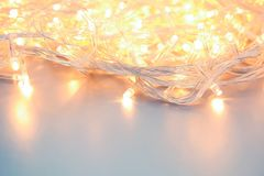 Glowing Christmas lights on table. Festive illumination. Glowing Christmas lights on table, closeup. Festive illumination stock image