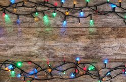 Glowing Christmas lights on wooden background. Top view stock images