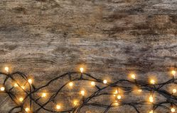 Glowing Christmas lights on wooden background. Top view stock image