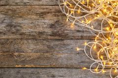 Glowing Christmas lights on wooden background. Top view Royalty Free Stock Photos