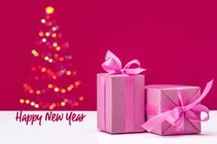 Glowing Christmas, New Year tree on pink background. Gifts in pink paper with ribbons. stock image