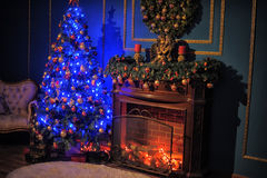 Glowing Christmas tree. By the fireplace Stock Photo