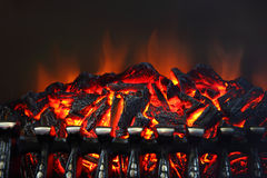 Glowing coals and fire flames in fireplace. With metal grating Royalty Free Stock Image