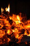 Glowing coals in the fireplace. Glowing coals and fire flames in the fireplace royalty free stock photos