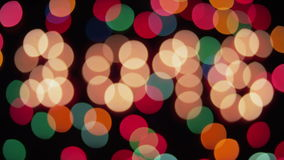Glowing 2016 and colored lights defocus 2016. On black background stock video