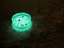 Glowing compass on a map. Fluorescent compass placed on a road map of Corsica royalty free stock photo
