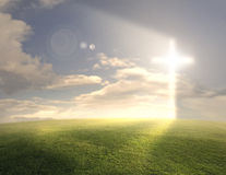 Glowing cross. Bright glowing cross on grassy background royalty free stock images