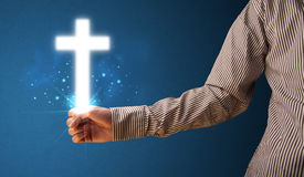 Glowing cross in the hand of a businessman Royalty Free Stock Images