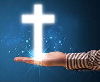 Glowing cross in the hand of a businessman Royalty Free Stock Image