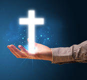 Glowing cross in the hand of a businessman Stock Photography