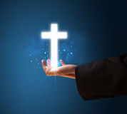 Glowing cross in the hand of a businessman Stock Photos