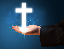 Glowing cross in the hand of a businessman Royalty Free Stock Photos
