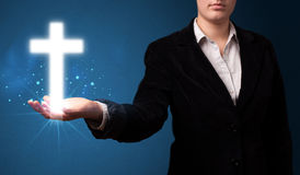 Glowing cross in the hand of a businesswoman Royalty Free Stock Images