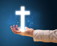 Glowing cross in the hand of a woman Stock Photos