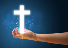 Glowing cross in the hand of a woman. Young woman holding a glowing cross in her hand Stock Images