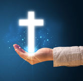 Glowing cross in the hand of a woman Stock Images