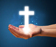 Glowing cross in the hand of a woman Stock Photo