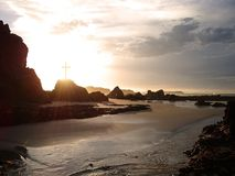 Glowing cross by the sea. Rays of light pass through a crucifix on a rocky coastline Stock Photo