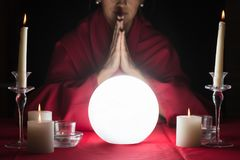 Fortuneteller With Clasped Hands And A Glowing Crystal Ball. Glowing Crystal Ball In Front Of Woman Fortuneteller With Clasped Hands stock photography