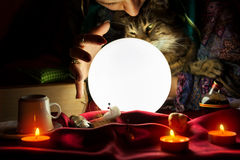 Glowing crystal ball with gypsy fortune teller who holds a cat. In the background stock photography