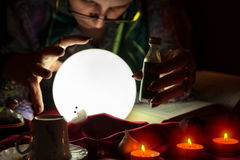Crystal ball and love potion in hands of fortune teller woman. Glowing crystal ball and love potion in hands of fortune teller woman Stock Image