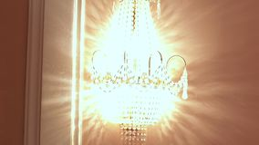 Glowing crystal sconce hanging on wall. Crystal chandelier stock footage