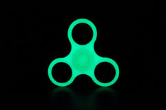 Glowing in the dark fidget spinner. Green glowing in the dark fidget spinner on black background Royalty Free Stock Photography