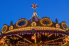 A glowing decoration of carousel on a dark blue sky at dusk. Evening in the amusement park. Old retro merry-go-round with illuminated light bulbs at sunset Stock Image