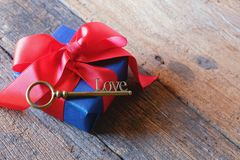 Glowing deep blue with red ribbon gift box and Love key shape on vintage wooden table. A present with love concept. Backdrop for. Valentine& x27;s day. Copy royalty free stock images