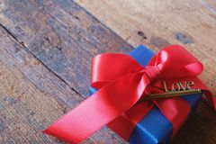 Glowing deep blue with red ribbon gift box and Love key shape on vintage wooden table. A present with love concept. Backdrop for. Valentine& x27;s day. Copy royalty free stock photos