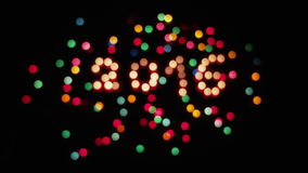 Glowing and defocus 2016 and colored lights. Glowing candles 2016 and colored lights on black background stock video