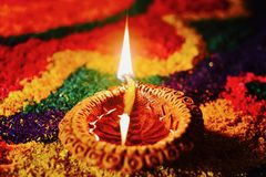 Rangoli with glowing diya. Glowing diya with rangoli in the background decorated on occasion of diwali festival Stock Photos