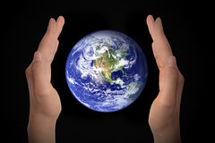 Glowing earth globe in hands on black, environment concept - elements of this image furnished by NASA. Glowing earth globe in hands on black background royalty free stock photography