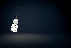 Glowing eco energy saving bulb hanging on wire in dark room Royalty Free Stock Photo