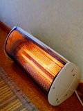 Glowing Electric Heater. A small radiant electric heater on the floor against a wall Stock Photos