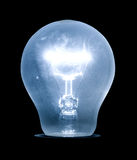 Glowing electric light bulb. Blue tint. Isolated on black Stock Photo