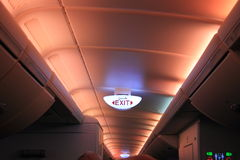 Glowing electrical exit sign on ceiling in Airbus A380 Royalty Free Stock Images