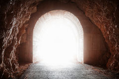 Glowing end of old tunnel. In red rock Royalty Free Stock Image
