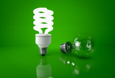 Glowing energy saving bulb and dark incandescent bulb over green stock images