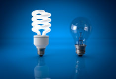 Glowing energy saving bulb and dead incandescent bulb over blueb Royalty Free Stock Photography