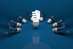 Glowing energy saving bulb among dead incandescent bulbs lying o royalty free stock image