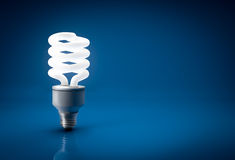 Glowing energy saving bulb over blue background Royalty Free Stock Photos