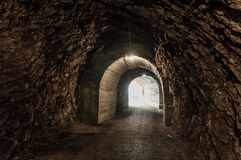 Glowing exit from dark abandoned tunnel.  Stock Image