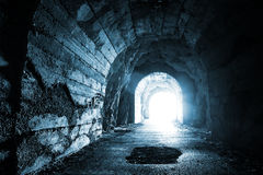 Glowing exit from dark abandoned tunnel. Monochrome blue photo Royalty Free Stock Photos