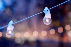 Glowing fairy lights outdoors at dusk. Glowing fairy lights for a party outdoors in a garden or park at dusk with selective focus, sparkling background bokeh and stock photography