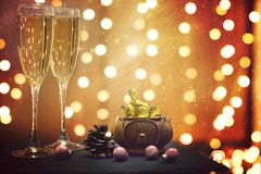 Glowing festive garland and champagne with candies on its background.  Stock Images