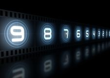 Glowing film strip. Countdown on black reflective background Royalty Free Stock Images